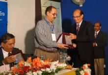 A crest is being handed over to Mr. M. Shamsul Islam Khan by M. Moniruzzaman