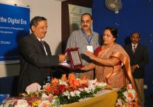 A crest is being handed over to Mr. Md. Eunusur Rahman by Ms. Shamsun Naher Khan Shapna